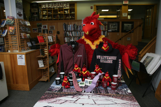 Swarthmore College mascot standing behind college bookstore merchandise display