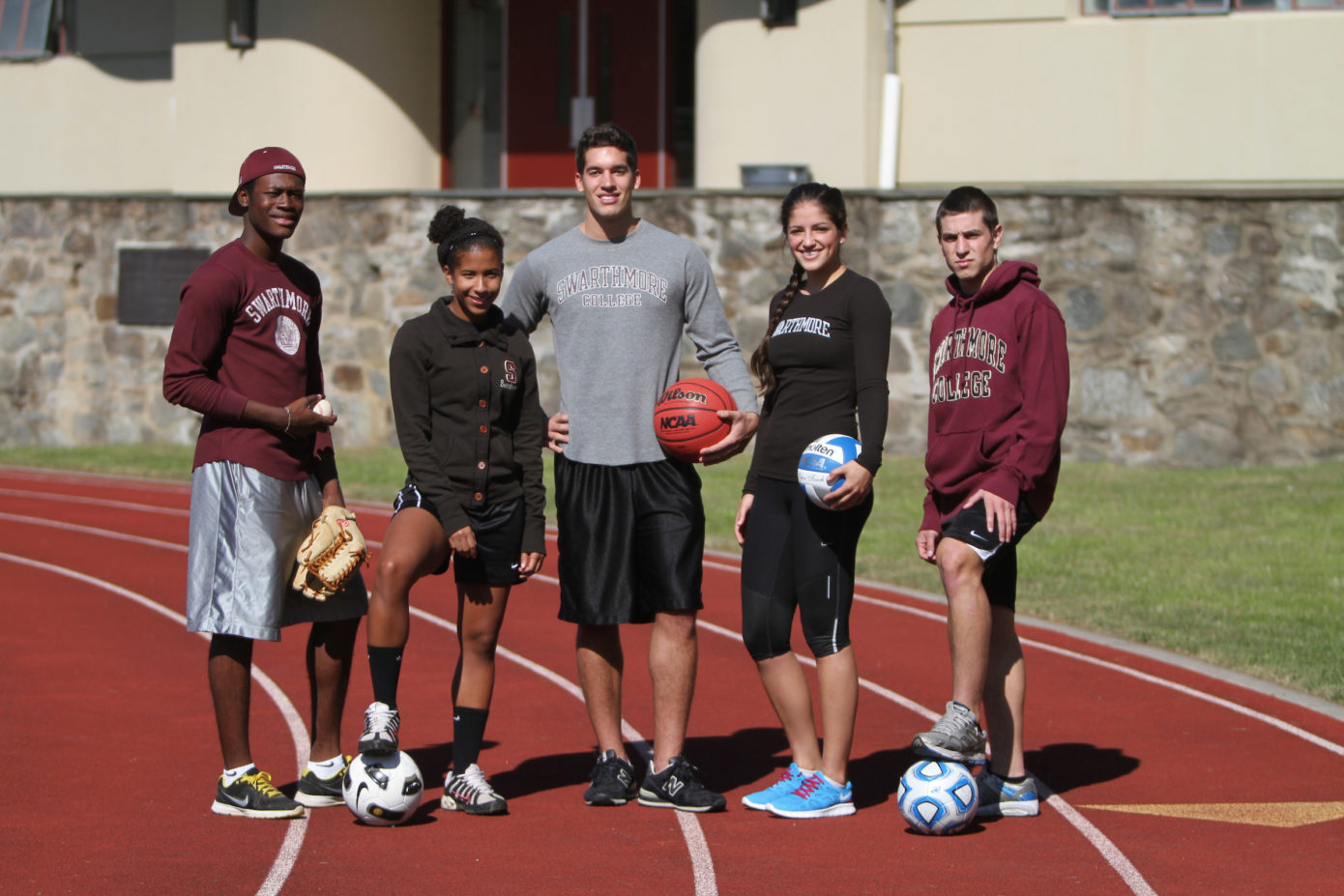 Swarthmore College student athletes standing on a track wearing college apparel and holding various balls and sporting equipment